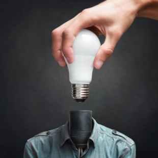 person holding white light bulb beside black bulb socket